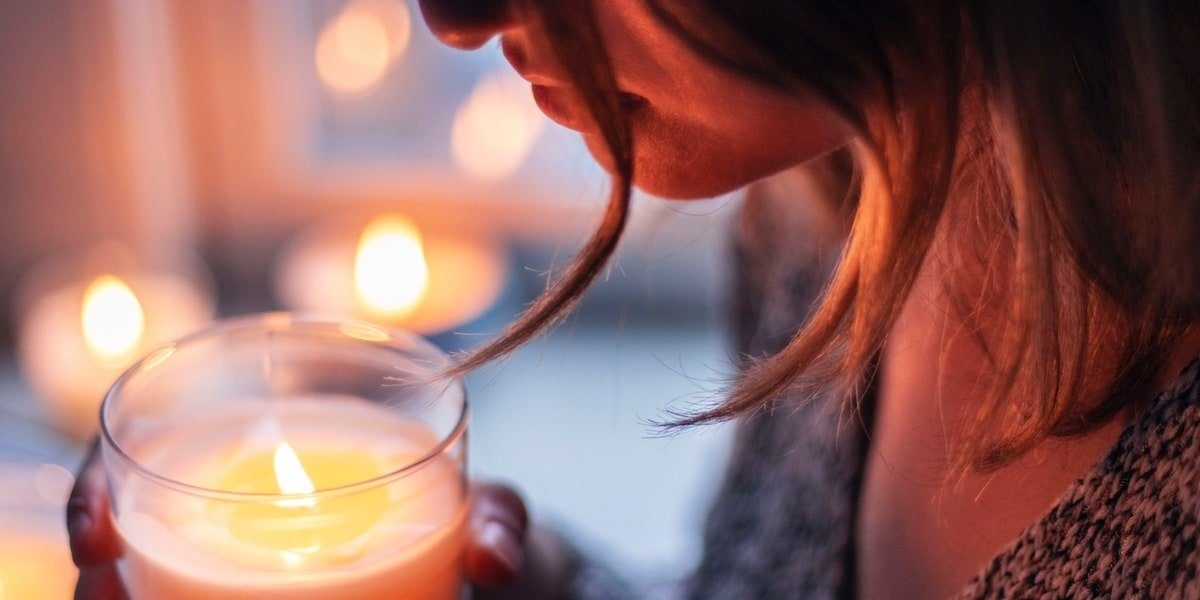 A woman smelling a soy wax candle